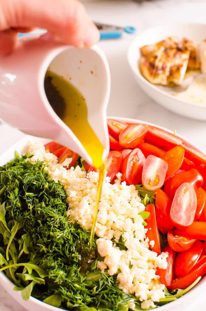 Pouring balsamic vinaigrette over Arugula Salad