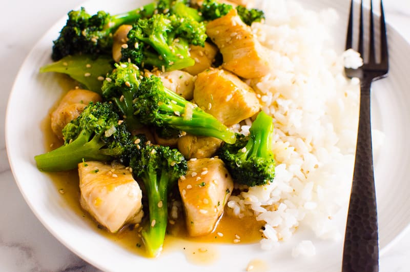 Chicken and Broccoli Stir Fry with white rice on white plate and black fork