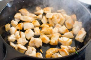 chicken cooking in cast iron skillet