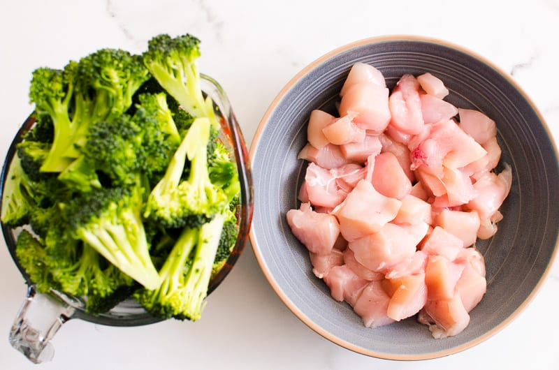 cut up chicken breast and broccoli in separate bowls