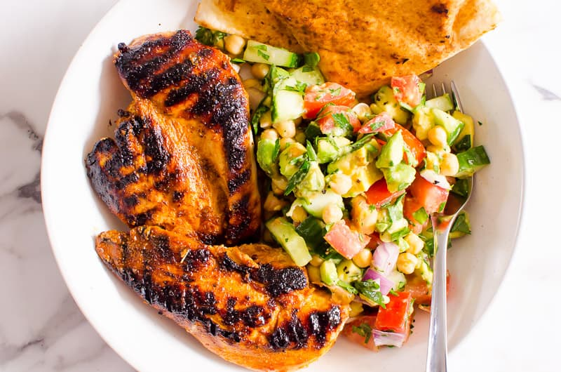 a bowl with chickpea salad, grilled chicken and pita bread