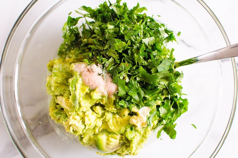 mashed avocado, cilantro, garlic and salt in a glass bowl