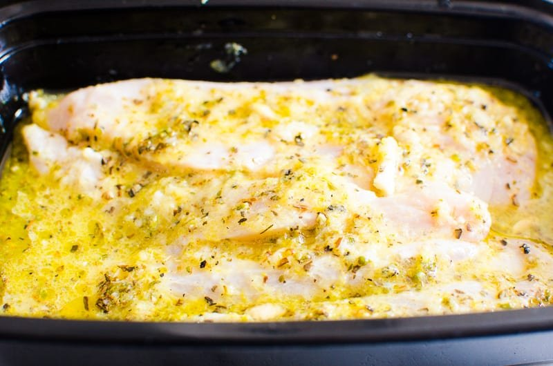 Grilled Chicken Breast marinating in a black container