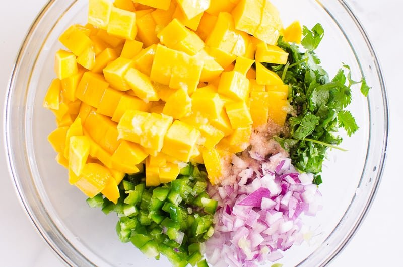 diced fresh mango, cilantro, red onion, jalapeno in glass bowl