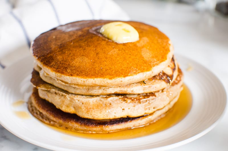 whole wheat pancakes stack on a plate with butter and maple syrup