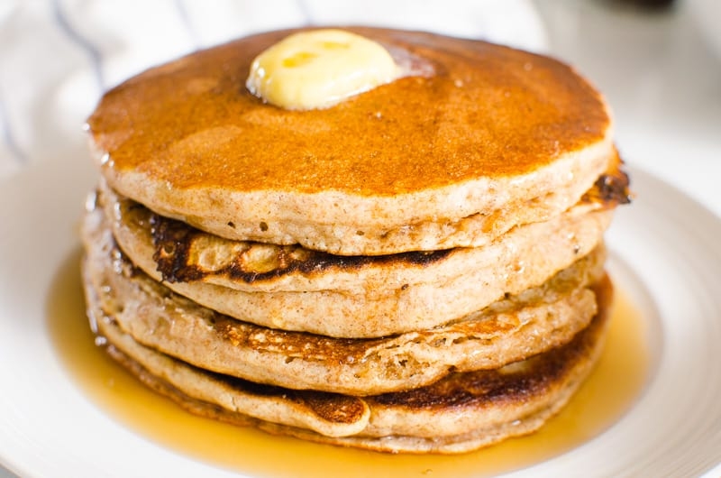 whole wheat pancakes stack on a plate with maple syrup and melted butter on top
