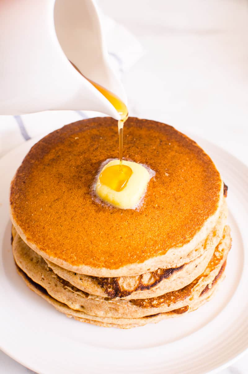 healthy pancakes stack with butter and pouring maple syrup on top