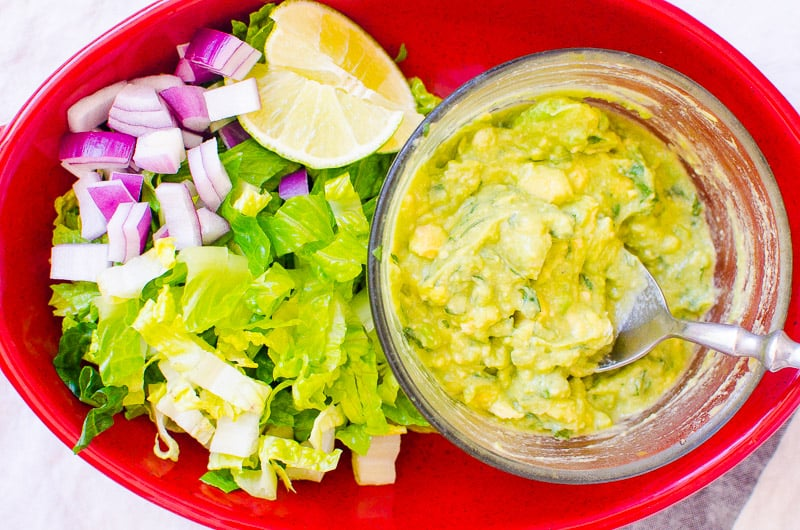 diced red onion, shredded lettuce, lime and guacamole in a red dish