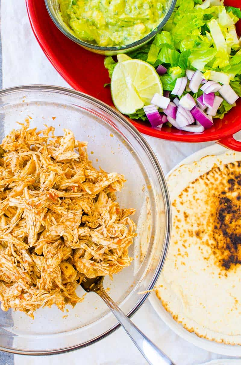 Cooked shredded chicken, tortillas and taco fixings in separate bowls