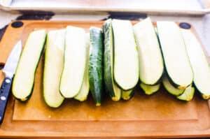 cut in halves zucchini on cutting board