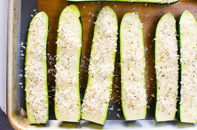 sliced zucchini sprinkled with cheese on a baking sheet