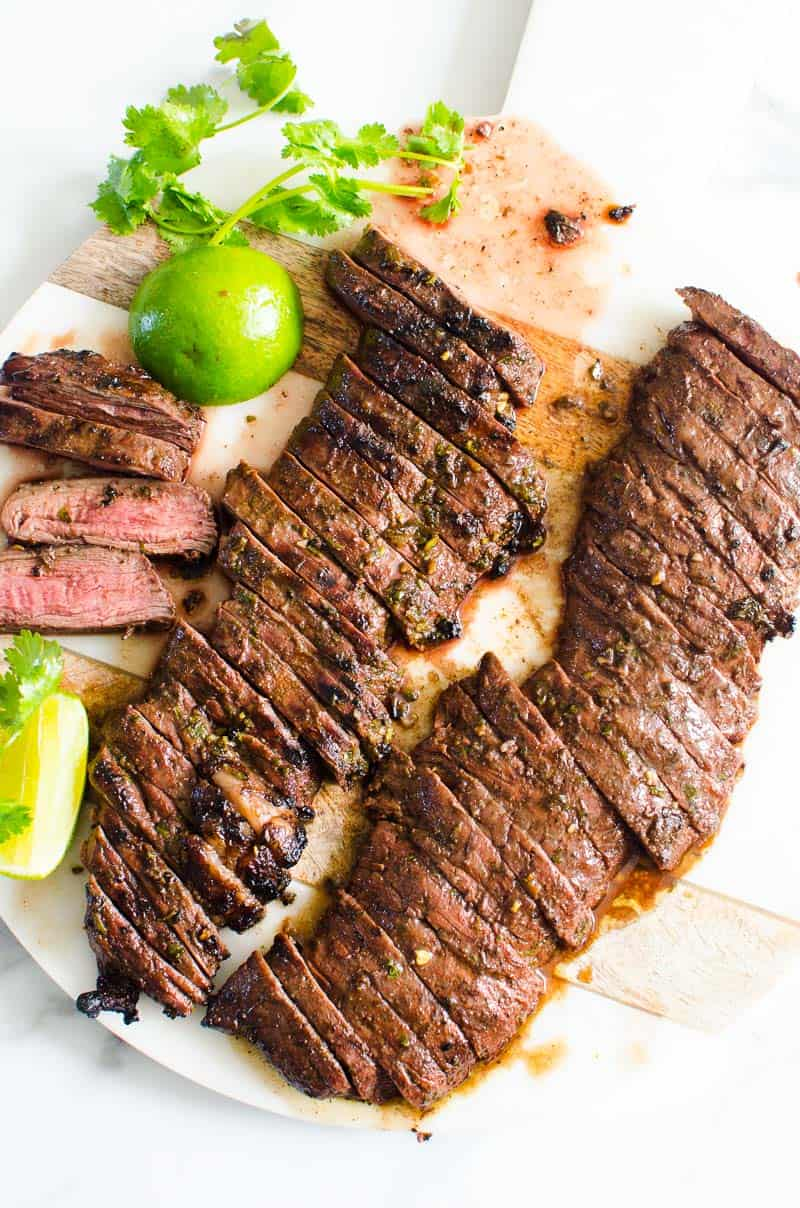 Carne Asada on a serving tray with lime and cilantro