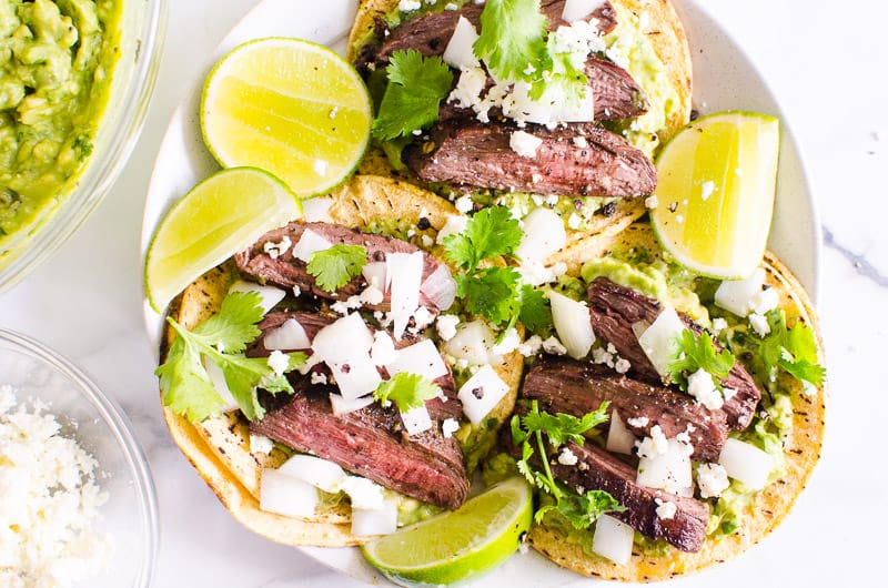 Carne Asada tacos served with lime, cilantro and guacamole