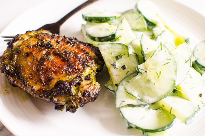 grilled chicken thighs served with cucumber salad on white plate and black fork