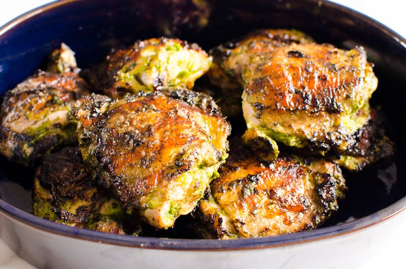 grilled chicken thighs in blue serving dish