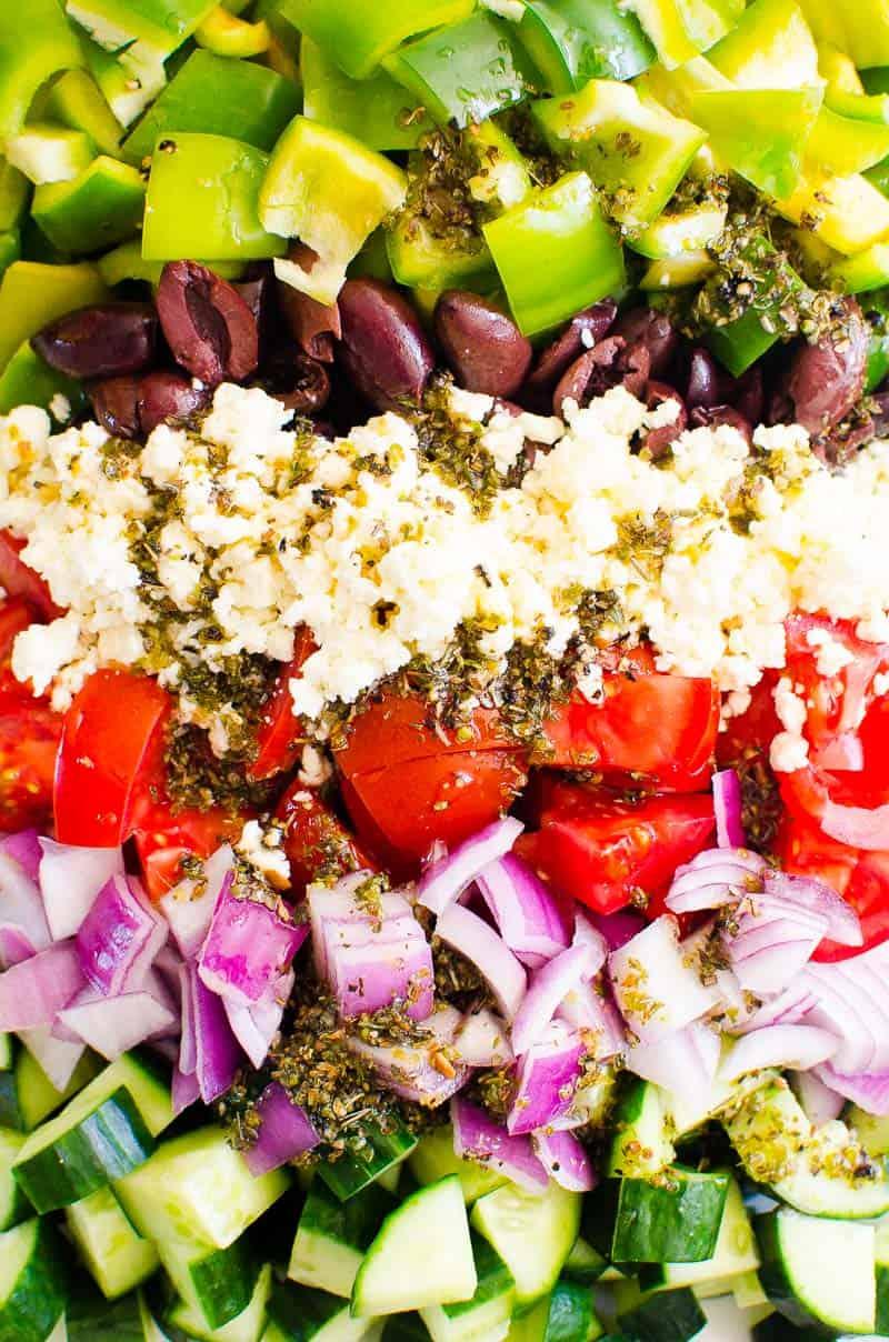 Los ingredientes de la ensalada griega incluyen pimiento, tomate, pepino, cebolla roja, aceitunas, queso feta y aderezo.