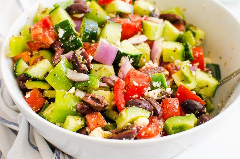greek salad in a bowl with spoon