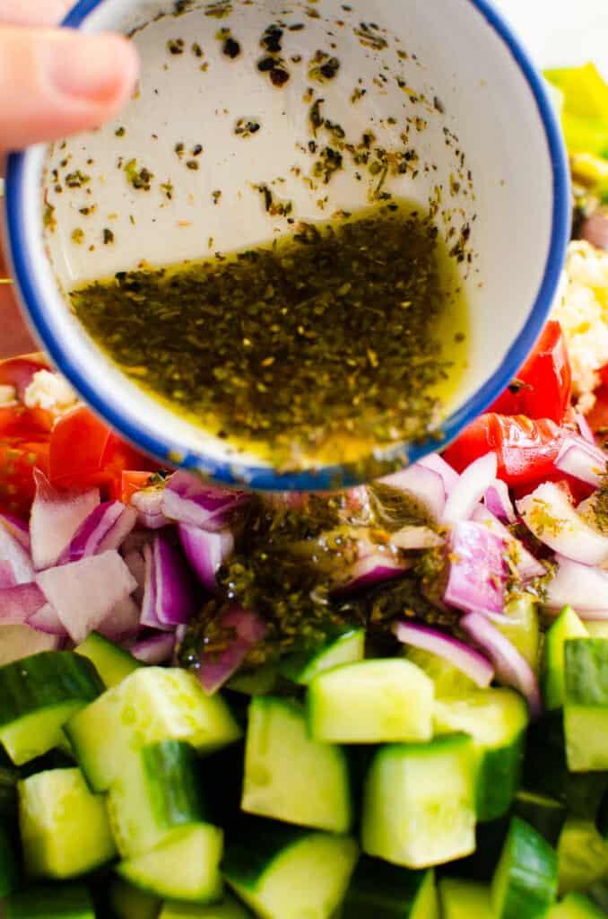 greek salad dressing being poured on greek salad vegetables