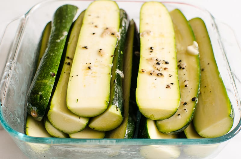 zucchini slices coated in dressing in baking dish