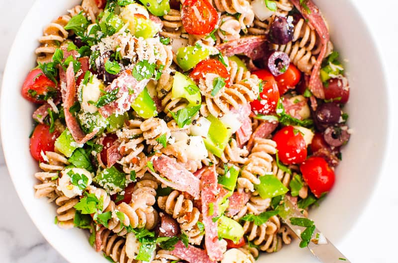 Italian pasta salad in white bowl with metal spoon