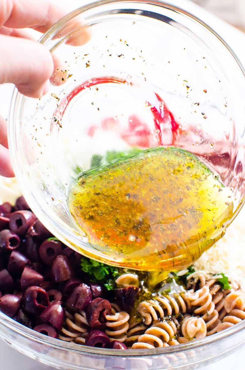 pouring italian dressing from a glass bowl over Italian Pasta Salad ingredients