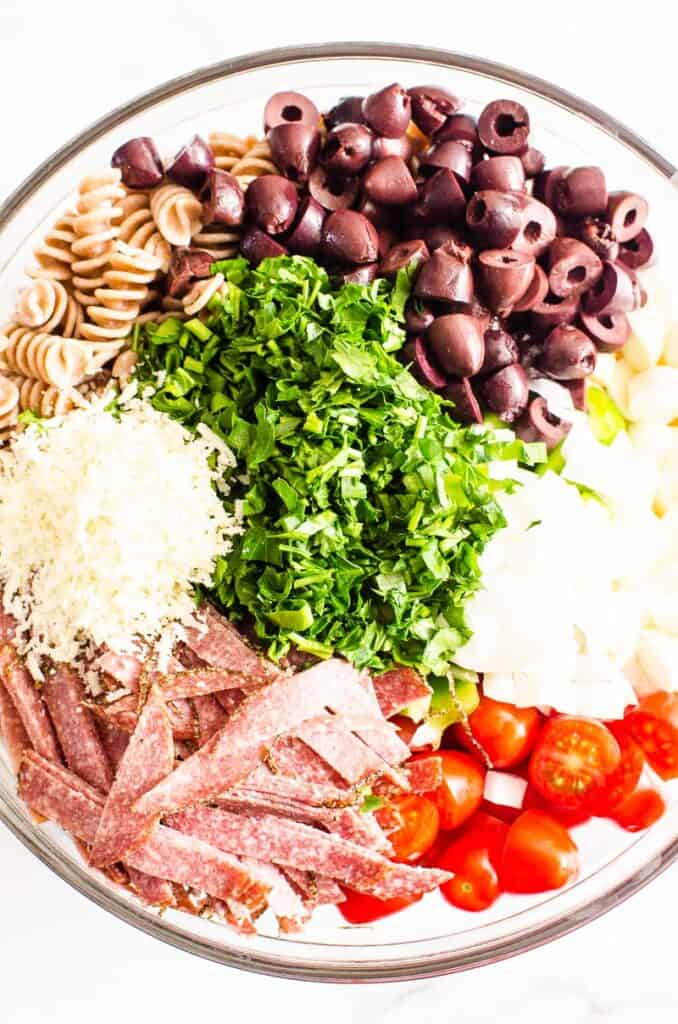 pasta, tomatoes, salami, olives, parsley, cheese in a bowl