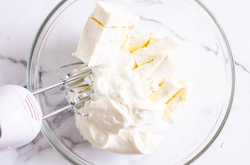 yogurt and cream cheese blended in a bowl with hand mixer