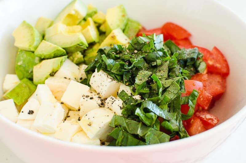 diced mozzarella cheese, tomatoes, avocado, basil in white bowl