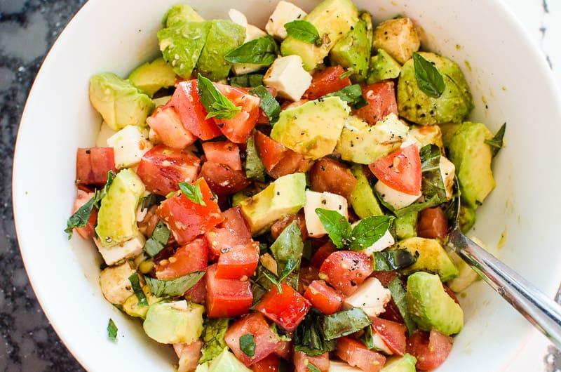 Tomato Mozzarella Salad in white bowl with metal spoon