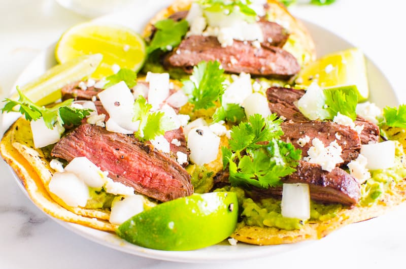 Carne Asada Tacos garnished with white onion, cilantro, cheese and lime