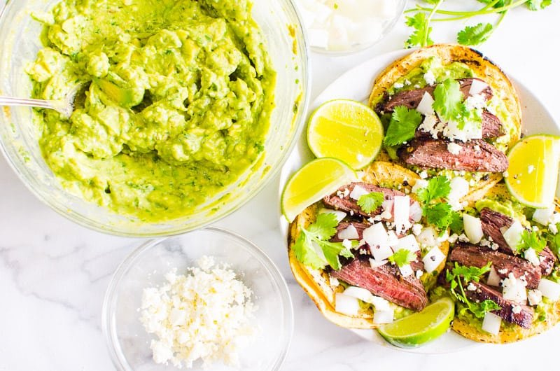 Carne Asada Tacos, guacamole in a bowl and crumbled feta cheese in a bowl
