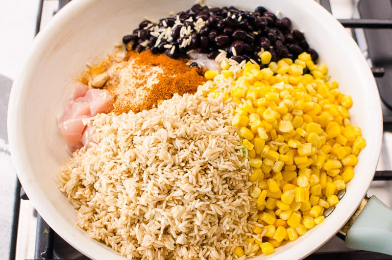 brown rice, corn, black beans, chicken and spices in a skillet