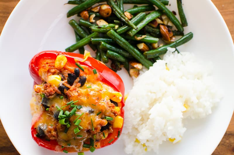 Mexican Stuffed Peppers with white rice and greens beans on white plate