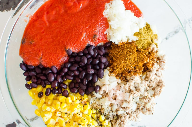 black beans, corn, rice, tomato sauce, seasonings in glass bowl