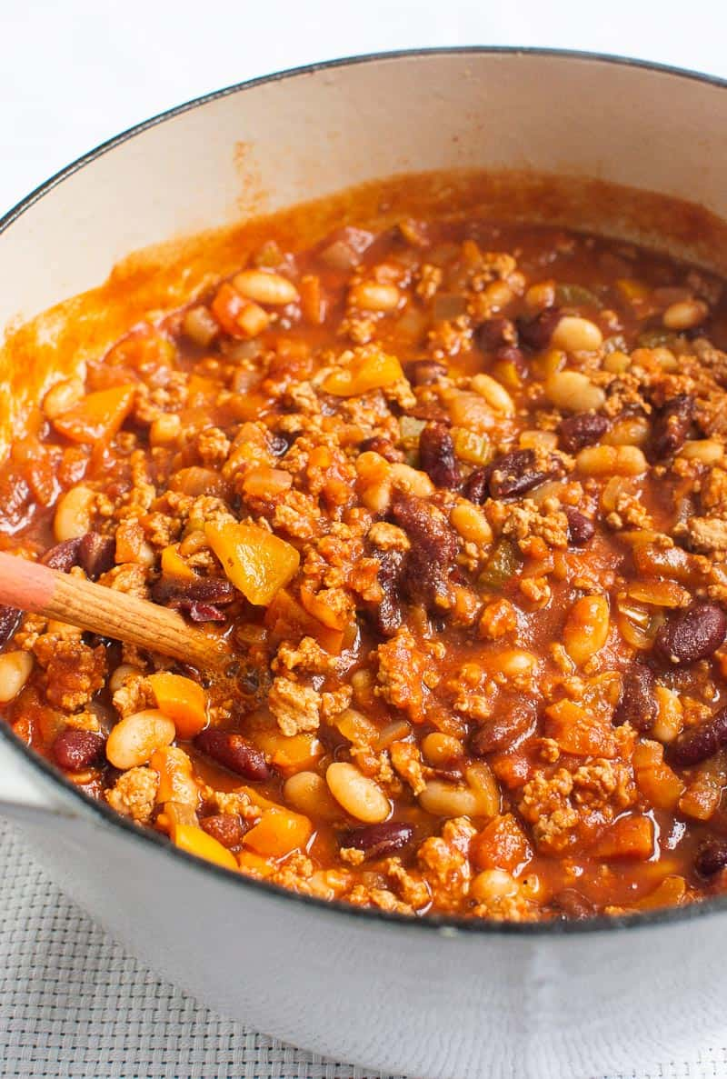 Turkey Chili in white pot with wooden spoon