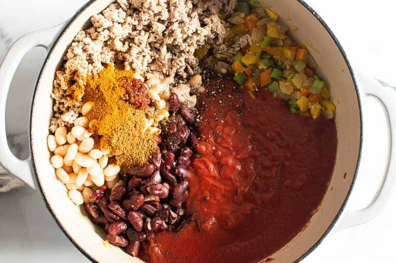 sauteed veggies, beans, turkey, spices and tomato sauce in white pot