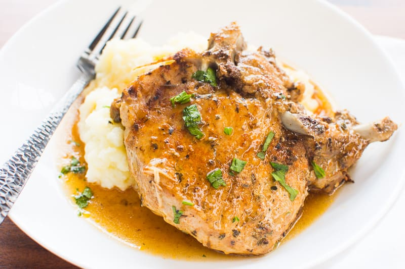 Instant Pot Pork Chops served over mashed potatoes with gravy