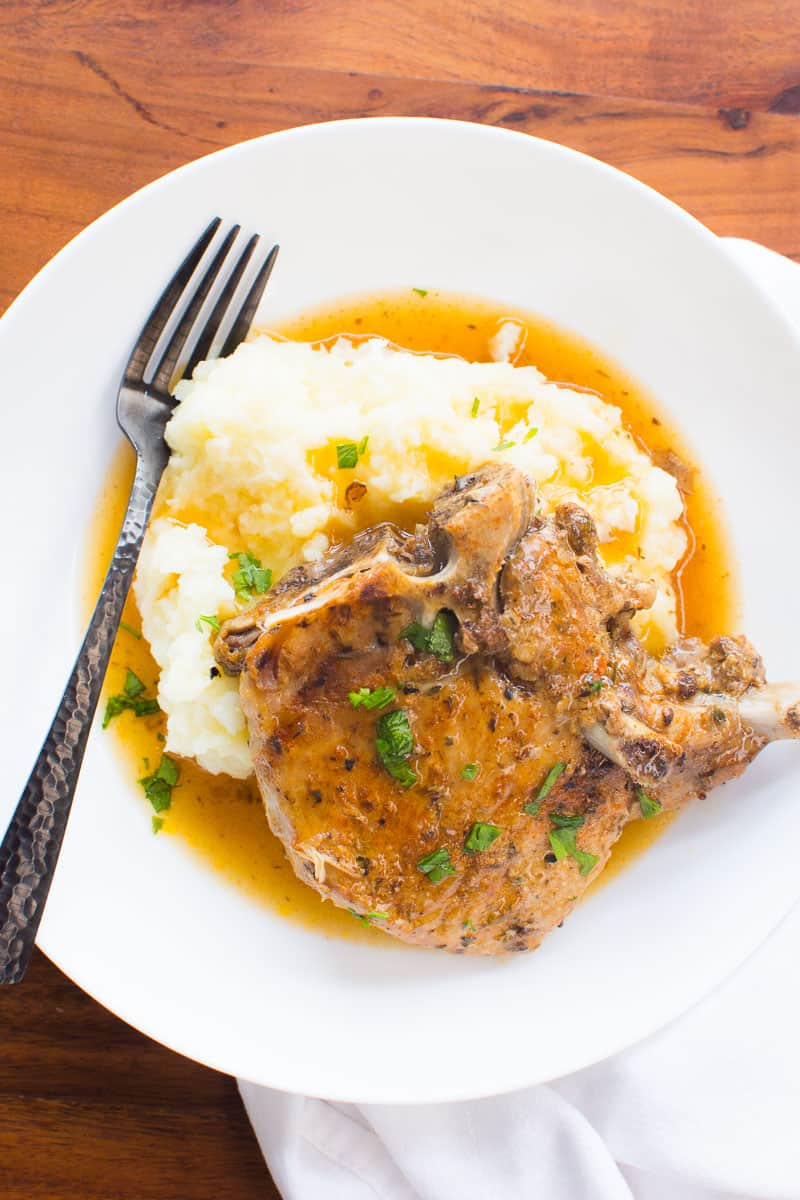Instant Pot Pork Chops served with gravy over mashed potatoes on white plate with fork