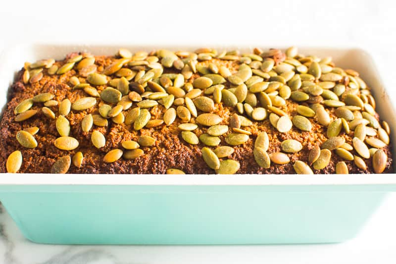 Almond flour pumpkin bread in light blue loaf pan topped with pumpkin seeds