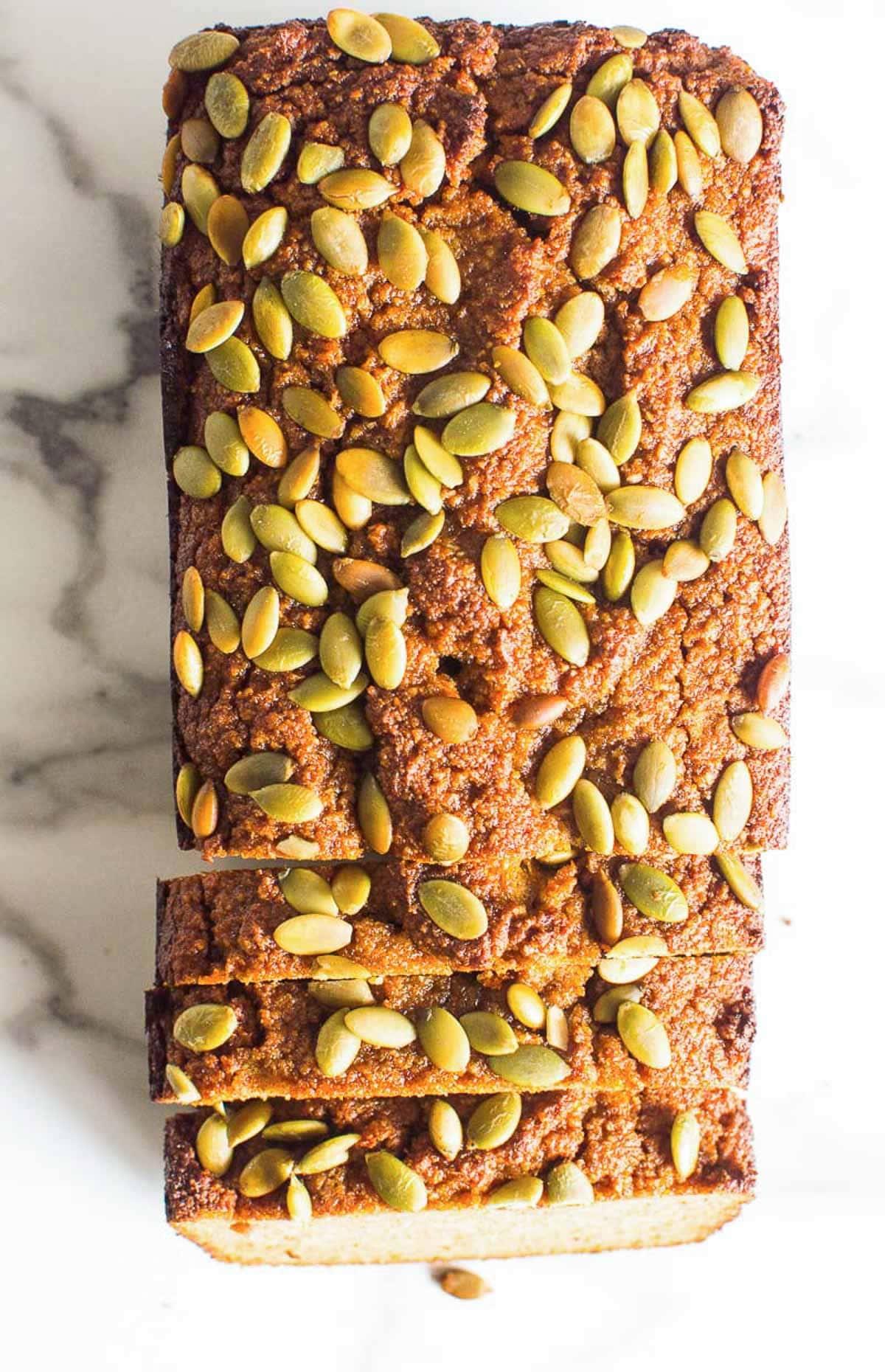 Almond Flour Pumpkin Bread with pumpkin seeds on top and sliced