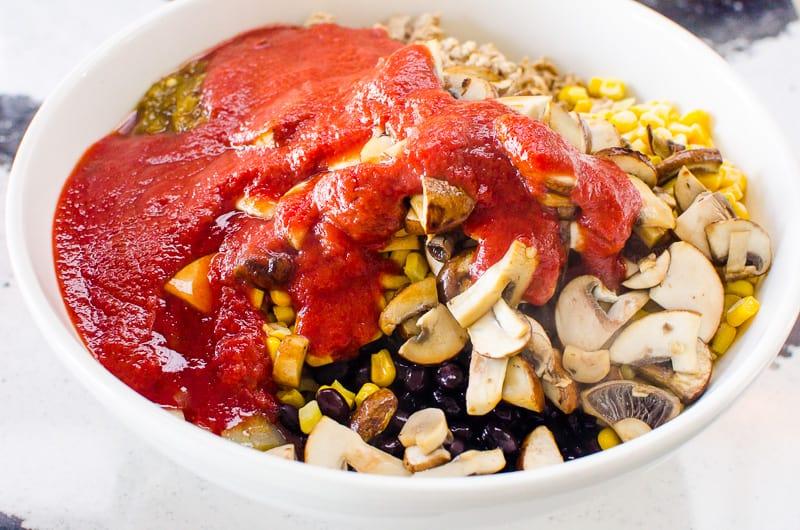 cuenco con champiñones, maíz, frijoles, carne y salsa de tomate