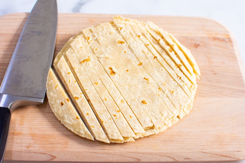 corn tortillas cut into strips on a cutting board