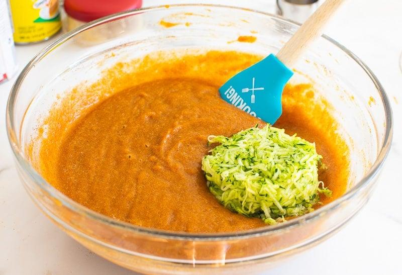 Masa de pastel de calabaza saludable con calabacín en recipiente de vidrio con espátula