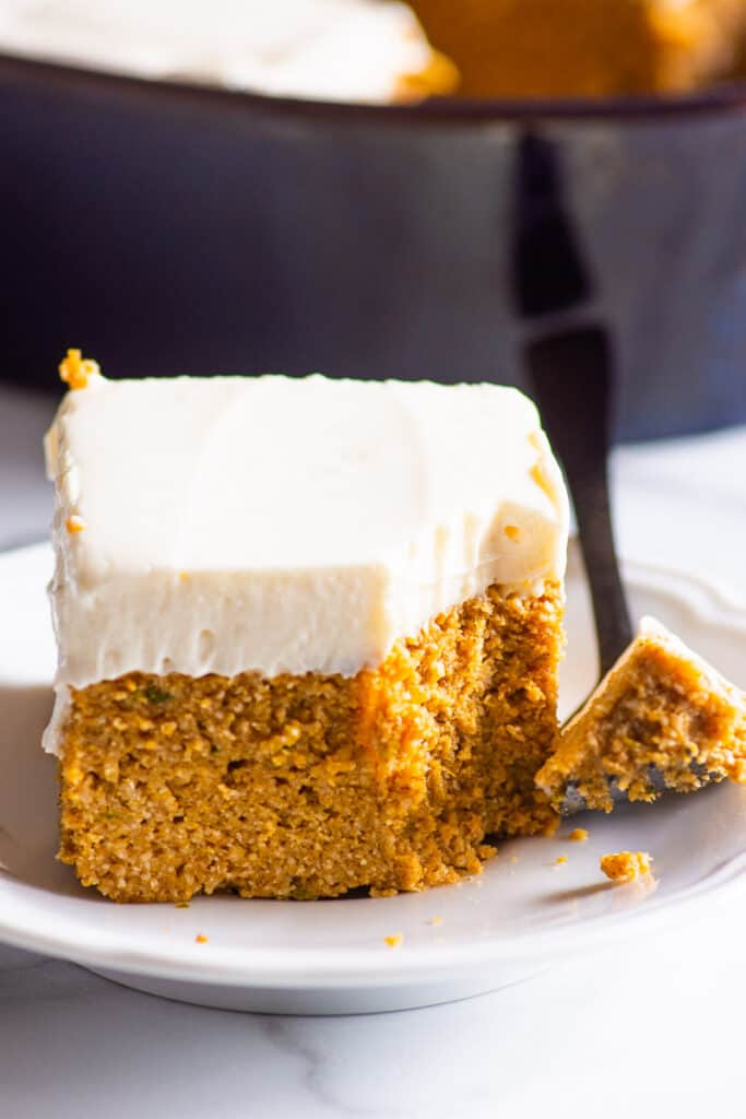 pumpkin cake slice on plate with fork and cake tin in background