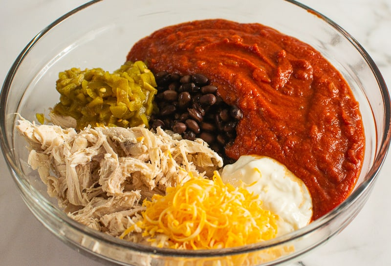 shredded chicken, enchilada sauce, cheese, yogurt, black beans and diced green chiles in a glass bowl