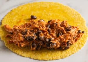 chicken enchiladas filling on top of tortilla