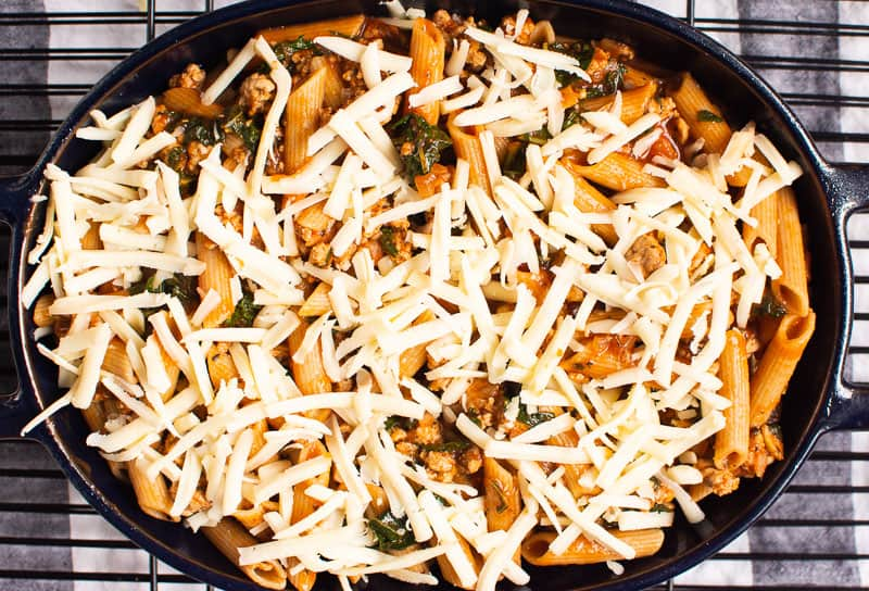 Ground Turkey Pasta Bake assembled and covered with shredded cheese