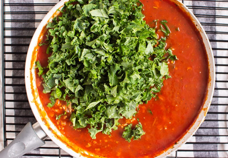 tomato sauce and kale in white skillet