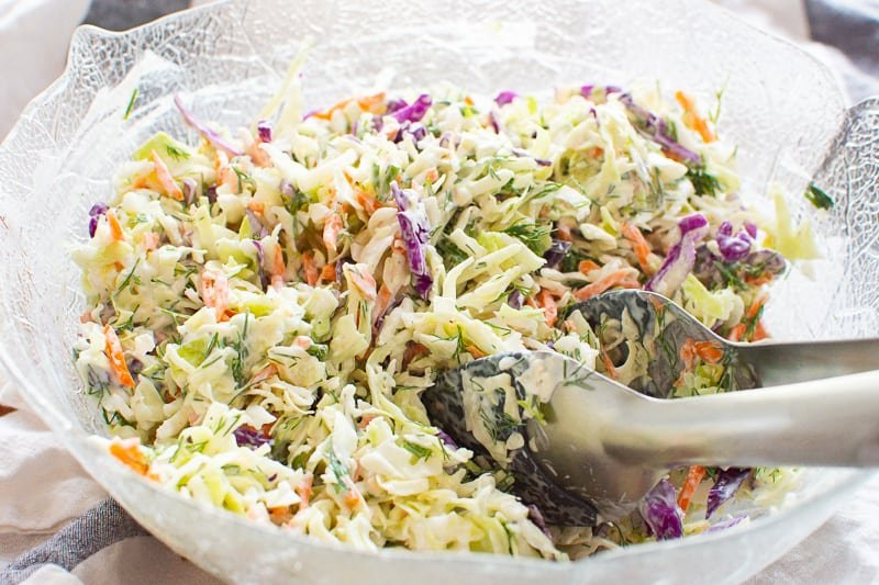 Healthy Coleslaw in glass bowl with tongs