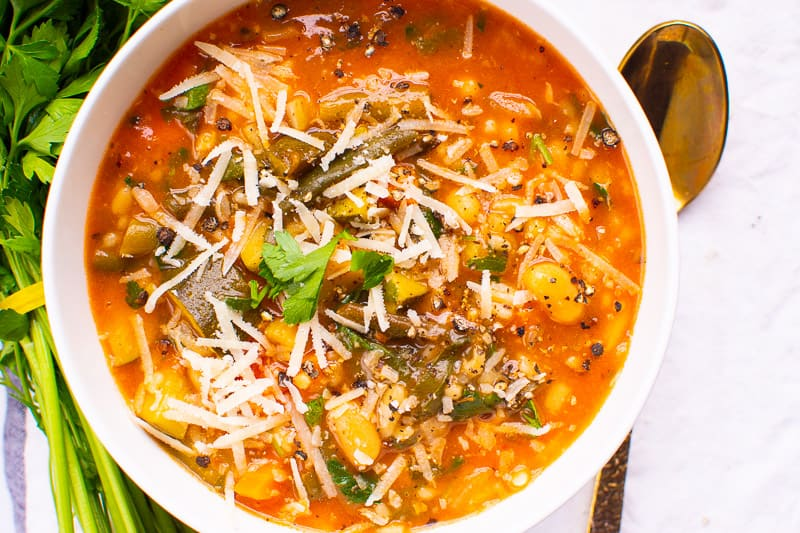 Minestrone Soup in white bowl garnished with parmesan cheese